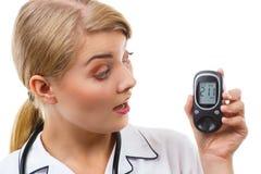 看glucometer,测量和检查糖水平,糖尿病的概念的震惊妇女 免版税图库摄影