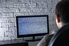 看lcd电视的小男孩在有顶楼的一个暗室称呼砖墙,后侧方视图 免版税库存图片