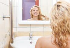 看Mirror& x27的愉快的白种人妇女; s反射和审查她的面孔和头发 免版税库存图片
