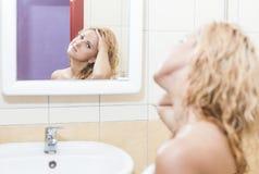 看Mirror& x27的愉快的白种人妇女; s反射和审查她的面孔和头发 免版税库存照片
