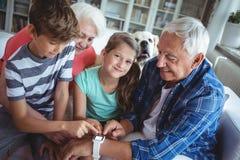 看smartwatch的祖父母和孙在客厅 免版税库存照片