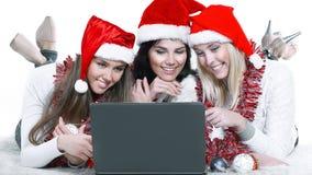 看t的圣诞老人服装的三个愉快的少妇 免版税库存照片