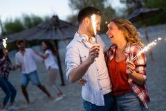 真实地愉快的嬉戏的夫妇获得乐趣在海滩 库存图片