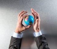 真正商人递拿着国际生态的概念的行星 库存图片
