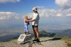 真正的人生的父亲和小孩在山顶部 免版税库存照片