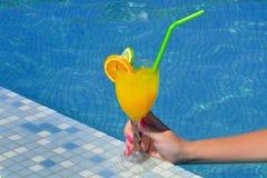 真正的女性在游泳池附近的秀丽饮用的鸡尾酒 库存照片