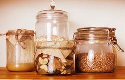 真正的有早餐成份的舒适木厨房在玻璃,蜂蜜,燕麦粥,牛奶, muesli关闭  库存图片