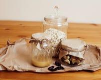 真正的有早餐成份的舒适木厨房在玻璃,蜂蜜,燕麦粥,牛奶, muesli,早晨食物关闭  免版税图库摄影