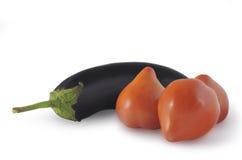 真正的自然在白色隔绝的茄子和三个红色蕃茄 免版税库存图片