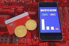 真正硬币,在塑料信用卡的bitcoins 有屏幕上bitcoin现金贸易的图的智能手机 10个背景蓝色董事会电路eps模式 哥斯达黎加 库存图片