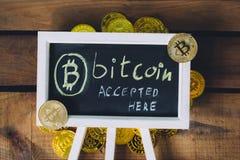 真正货币Bitcoin接受了这里签署与延长真正的bitcoins的木背景 免版税图库摄影