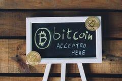 真正cVirtual货币Bitcoin接受了这里签署与真正的bitcoins的木背景在角落 图库摄影
