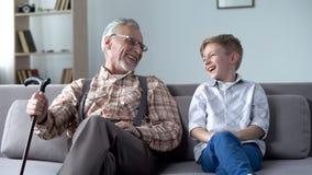 真诚地笑的祖父和的孙子,一起耍笑,可贵的乐趣片刻 免版税库存图片