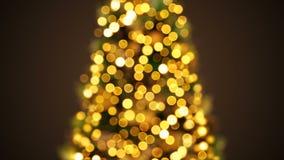 眨眼睛在Defocused迷离Bokeh的美好的金黄新年树光 招呼背景无缝的3d动画 快活 影视素材