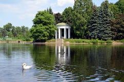 眺望台圆形建筑在天鹅池塘岸  库存图片