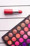 眼影和红色唇膏擦亮剂在白色木背景 免版税图库摄影