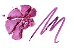 眼影膏紫罗兰和唇膏书写在白色被击碎隔绝的紫罗兰 库存照片