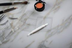眼影调色板、刷子、假鞭子、镊子和人为眼皮折痕双重磁带眼睛构成的在大理石秀丽书桌上 库存照片