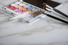 眼影调色板、刷子和人为眼皮折痕双重磁带眼睛构成的在大理石秀丽书桌桌上 库存照片