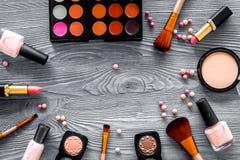 眼影调色板,刷子,唇膏,在裸体颜色的胭脂为在灰色背景顶视图copyspace组成 免版税库存照片