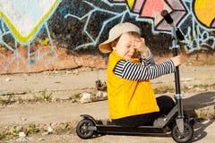 眼泪汪汪的年轻男孩坐他的滑行车 库存图片