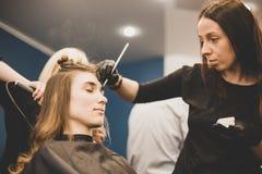 眼眉洗染 大师绘有无刺指甲花的眼眉给美女,绘与在美容师构成的沙龙的一把刷子 免版税库存照片