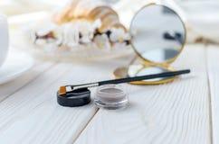 眼眉的刷子和阴影唇膏在咖啡桌上 免版税图库摄影