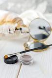 眼眉的刷子和阴影唇膏在咖啡桌上 库存照片