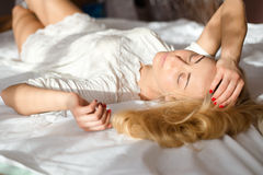 眼睛结束了有吸引力嫩少妇美好性感白肤金发女孩睡觉的或放松的说谎在阳光下光束或光芒 免版税库存图片