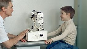 眼科医生在有坐在椅子的小男孩的检查屋子里调查眼睛测试机器 免版税库存照片