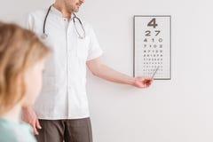 眼科医生显示男孩一张眼睛测试图 免版税图库摄影