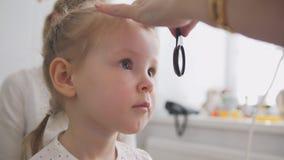 眼科学诊所的逗人喜爱的孩子-验光师诊断小白肤金发的女孩 免版税库存照片