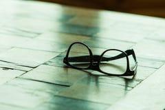 眼镜在一张方格的桌上的 库存图片