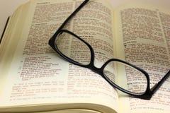 眼镜在一部开放圣经的 免版税库存图片