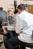 眼镜师与被切开的灯的审查的男孩的眼睛 库存照片