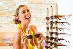 眼镜师购物太阳镜的少妇 免版税库存图片
