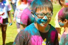 戴眼镜新春佳节的一个颜色上漆的男孩 免版税库存图片