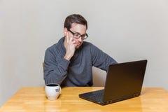 戴眼镜的一个人研究膝上型计算机 免版税库存图片