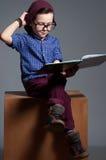 戴眼镜的一个蓝眼睛的孩子 男孩坐与很严肃 免版税库存图片
