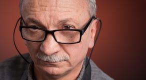 戴眼镜的一个年长人 免版税库存照片