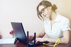 戴眼镜的可爱的女孩键入在膝上型计算机的 库存照片