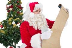 戴眼镜的圣诞老人读羊皮纸的 库存图片