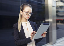 戴眼镜的女商人使用片剂 免版税库存照片