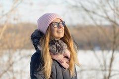 戴眼镜的女孩在自然的冬天享用太阳 库存照片