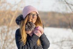 戴眼镜的女孩在自然的冬天享用太阳 免版税库存照片