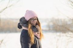 戴眼镜的女孩在自然的冬天享用太阳 免版税图库摄影