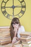 戴眼镜的女孩读了书惊奇的某事 免版税库存图片