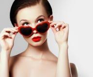 戴眼镜的女孩以心脏的形式 假日构成 免版税库存照片