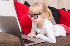 戴眼镜的孩子使用计算机 免版税图库摄影