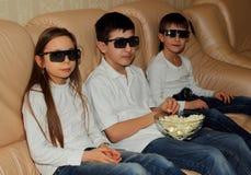 戴眼镜的孩子观看3D电影 免版税库存照片